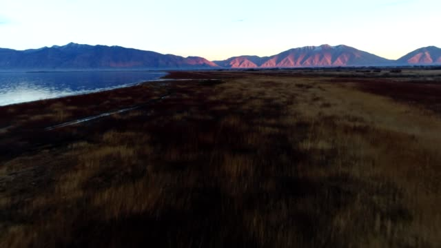 a drone flies over a lake towards mountains during sunset in provo utah - provo stock-videos und b-roll-filmmaterial