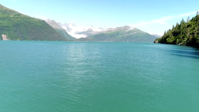 a drone flies over a light blue lake in whittier alaska - prince william stock videos & royalty-free footage