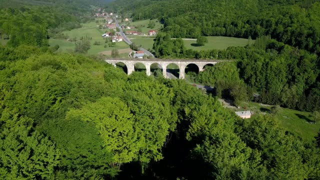 a drone flies over a railway bridge of teliu in prejmer brașov county romania - transilvania video stock e b–roll
