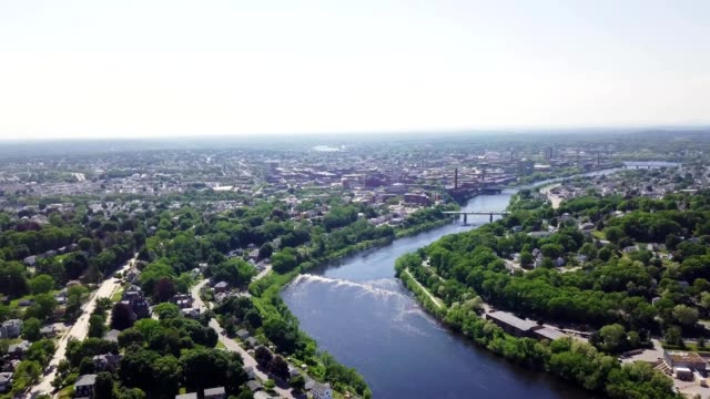 a drone flies over a river in lowell massachusetts - lowell stock videos & royalty-free footage