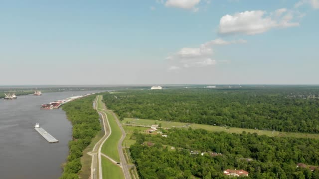 a drone flies over a riverfront road towards mississippi river in chalmette louisiana - louisiana video stock e b–roll