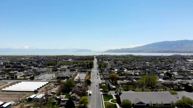 a drone flies over a road on a clear day in lehi utah - lehi stock videos & royalty-free footage
