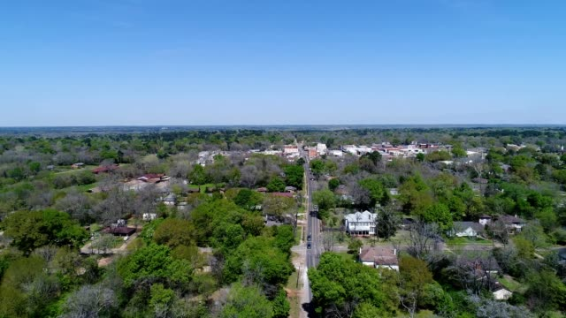 a drone flies over a small town road in crockett texas - small town stock videos and b-roll footage