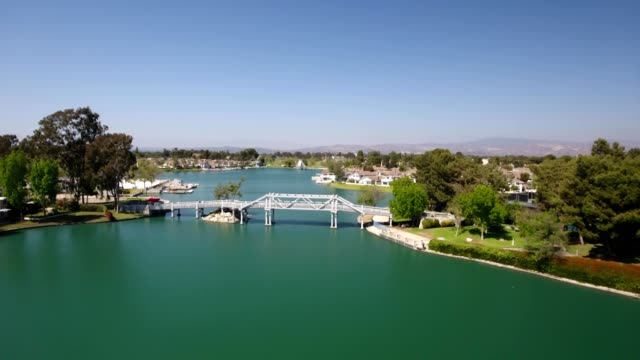 a drone flies over a woodbridge over a lake in irvine california - irvine california stock videos & royalty-free footage