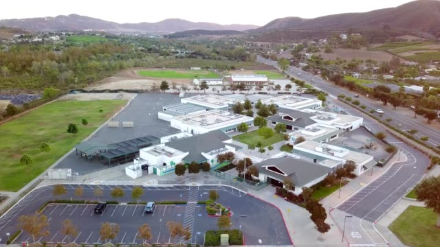a drone flies over an elementary school in san marcos california - 小学校点の映像素材/bロール