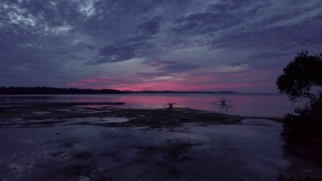 a drone flies over an island beach reflecting a res sunset in manila philippines - manila philippines stock videos and b-roll footage