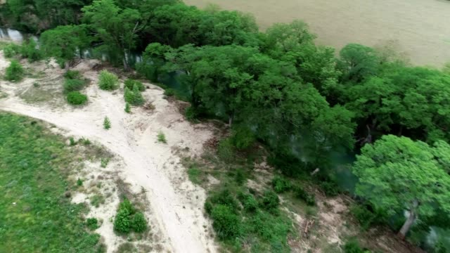 a drone flies over cleared area by the blanco river in wimberley texas - dronebase stock videos and b-roll footage