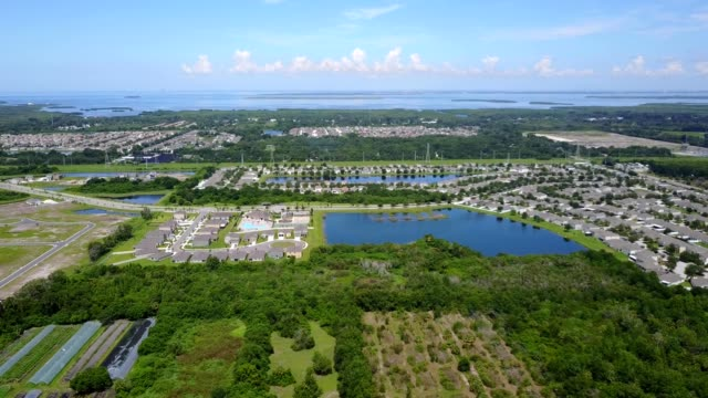 a drone flies over esidential areas towards tampa bay in riverview florida - tampa stock videos & royalty-free footage
