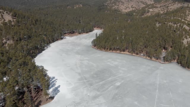 a drone flies over frozen center lake in custer south dakota - カスター州立公園点の映像素材/bロール