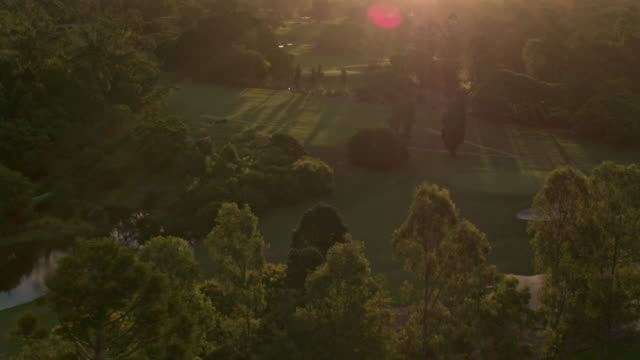 drone flies over golf course and parkland at sunset - golf stock videos & royalty-free footage