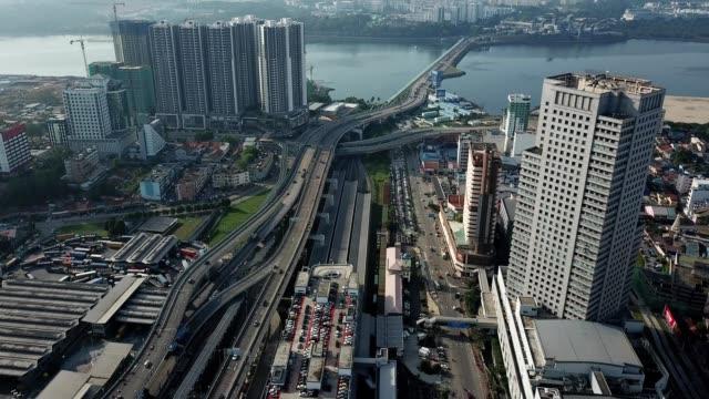 a drone flies over johor bahru city towards the causeway bridge in malaysia - causeway stock videos & royalty-free footage