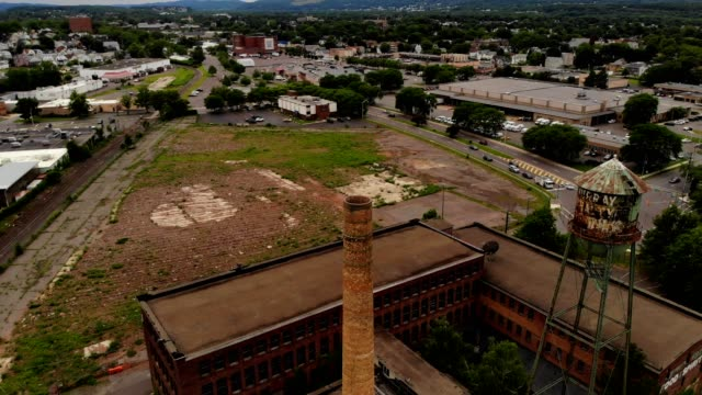 a drone flies over old murry's holding complex and smoke stack in wilkes-barre pennsylvania - wilkes barre stock videos & royalty-free footage
