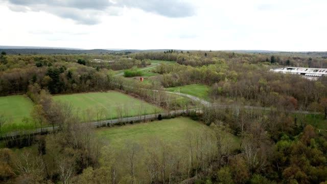 a drone flies over open fields by a school in tannersville pennsylvania - poconobergen bildbanksvideor och videomaterial från bakom kulisserna