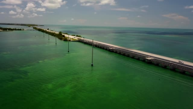 stockvideo's en b-roll-footage met a drone flies over power lines towards a intracoastal waterway to key largo florida - the florida keys