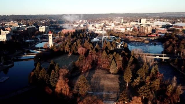 vídeos de stock, filmes e b-roll de a drone flies over spokane river and monroe street bridge at sunrise in spokane washington - estado de washington