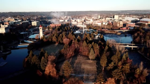 a drone flies over spokane river and monroe street bridge at sunrise in spokane washington - stato di washington video stock e b–roll