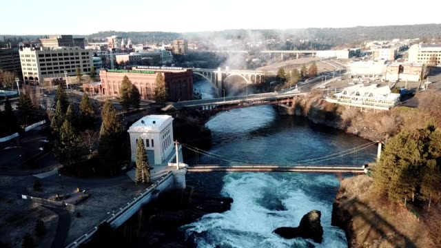 a drone flies over spokane river and monroe street bridge at sunrise in spokane washington - pacific northwest usa stock videos & royalty-free footage