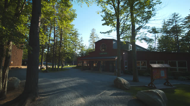 drone flies over summer camp lodge building surrounded by trees - entrance sign stock videos & royalty-free footage