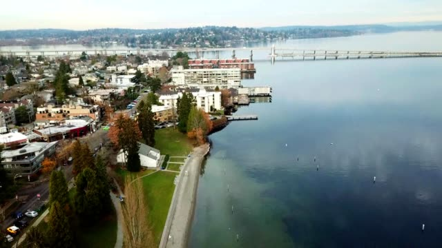 a drone flies over the coast of madison park north beach in seattle washington - washington state stock videos & royalty-free footage