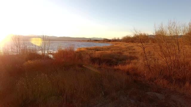 A drone flies over Utah lake during sunset in American Fork Utah