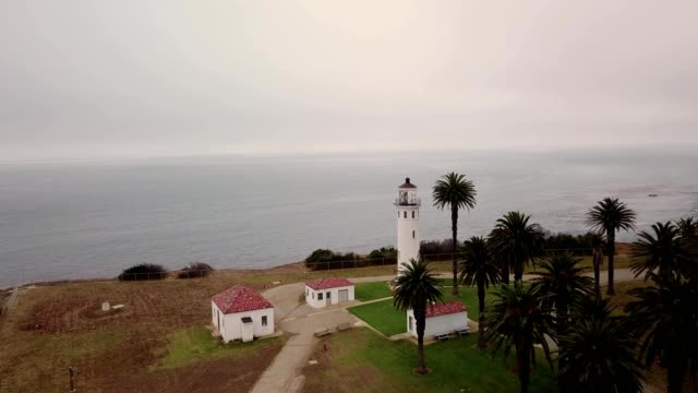 a drone flies past a lighthouse towards the ocean in point vicente rancho palos verdes california - palos verdes stock videos & royalty-free footage