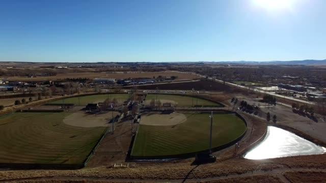 a drone flies past baseball diamonds in broomfield colorado - hay maze stock videos & royalty-free footage