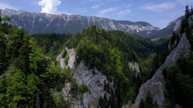 A drone flies through mountains towards Piatra Crailului at the Zărnești gorge in Brașov County Romania