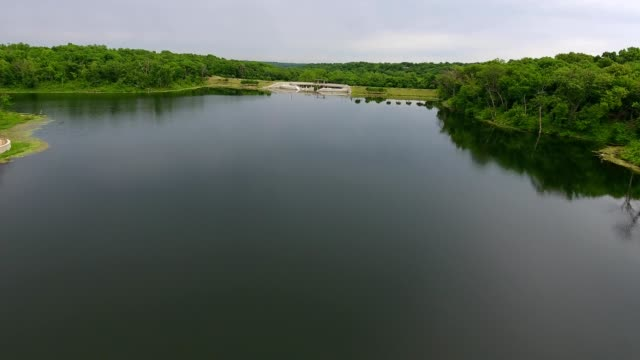 vídeos de stock e filmes b-roll de a drone flies toward a dam in lenexa kansas - kansas