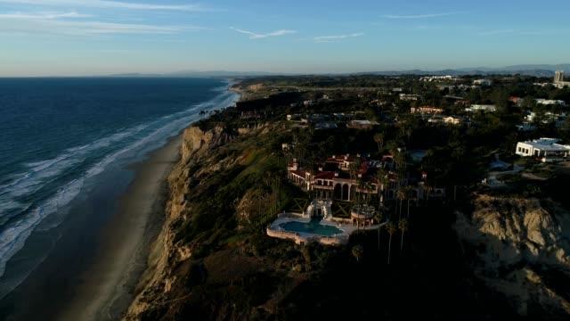 A drone flies towards a cliffside mansion in San Diego California