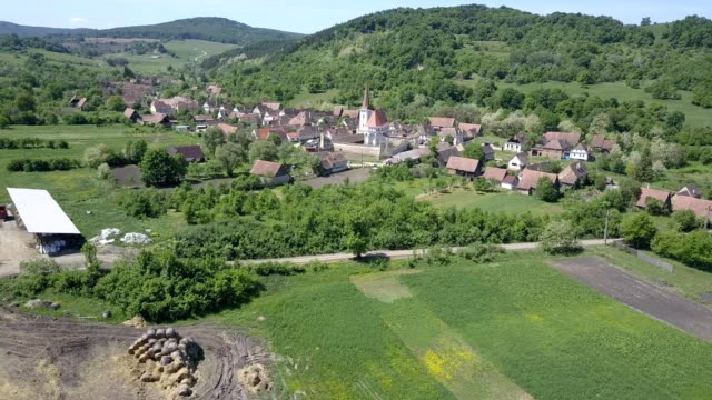 a drone flies towards a fortified church in cloasterf romania - mures stock videos and b-roll footage