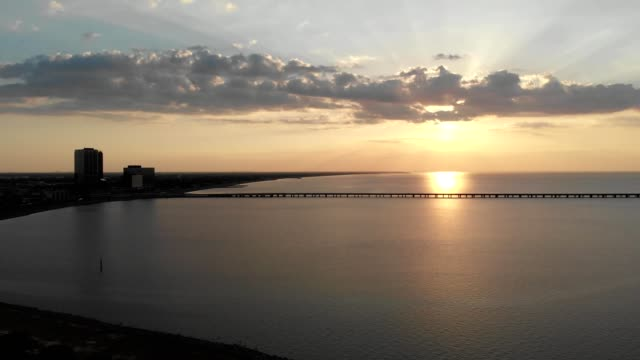 A drone flies towards a sunset by the Lake Pontchartrain Causeway Bridge in New Orleans Louisiana