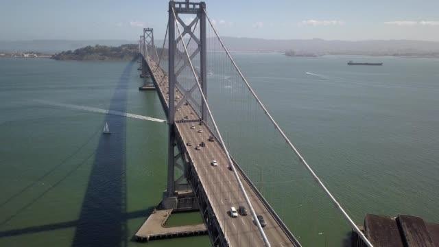 a drone flies towards bay bridge in san francisco california - san francisco bay stock videos and b-roll footage