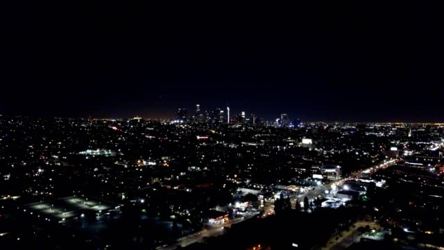 A drone flies towards downtown Los Angeles California at night