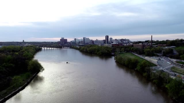 a drone flies towards downtown richmond virginia over the james river - バージニア州 リッチモンド点の映像素材/bロール