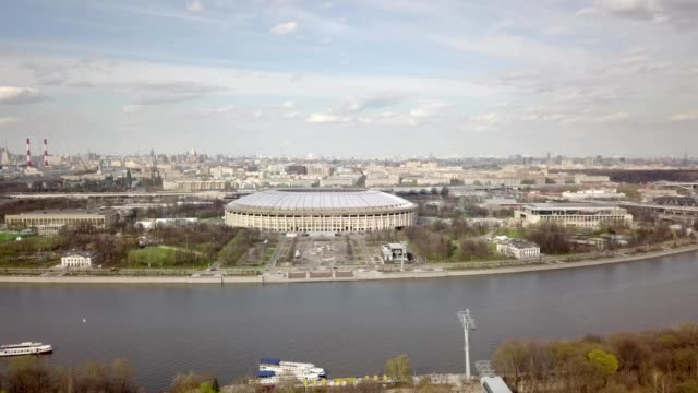 A drone flies towards Luzhniki Stadium from across Moscow River in Moscow Russia