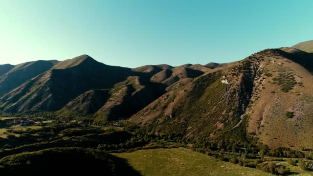 A drone flies towards mountains in Big Springs Park in Provo Utah