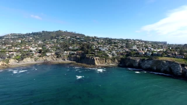 A drone flies towards the cliffs of La Jolla San Diego California