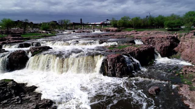 A drone flies up a river water flowing through rocks and falls in Sioux Falls South Dakota
