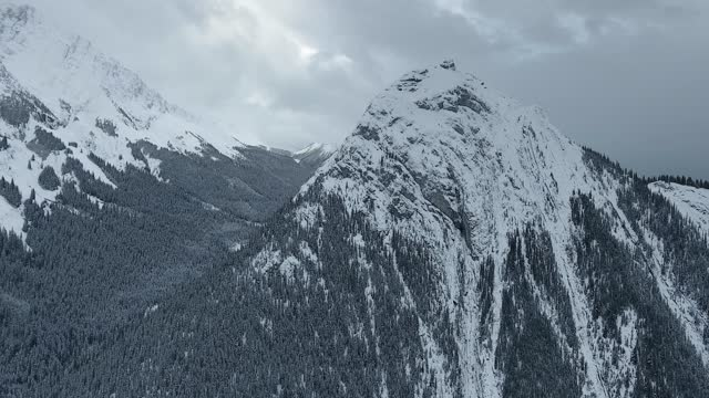 drone flies up to the majestic frozen mountain covered with thick layer of snow and forest in kananaskis, alberta, canada - majestic stock videos & royalty-free footage