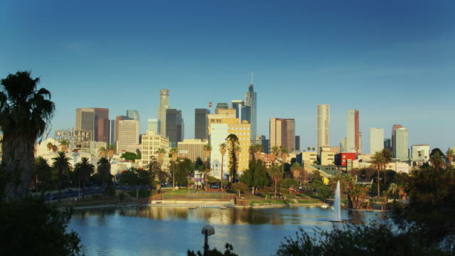 drone flight across macarthur park approaching downtown los angeles - city of los angeles stock-videos und b-roll-filmmaterial