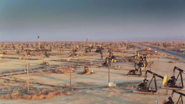 drone flight across vast california oil field - trivella petrolifera video stock e b–roll
