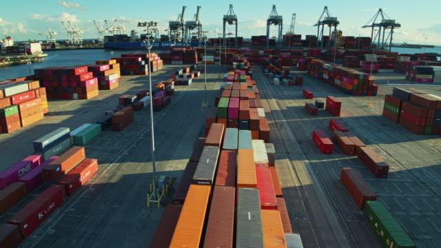 vídeos y material grabado en eventos de stock de drone flight along a line of stacked containers in shipping terminal - long beach los ángeles