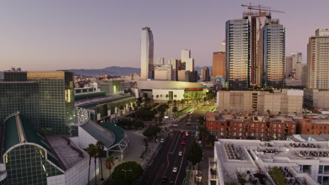 drone flight along figueroa street looking towards los angeles convention center and la live - microsoft theater los angeles stock videos & royalty-free footage