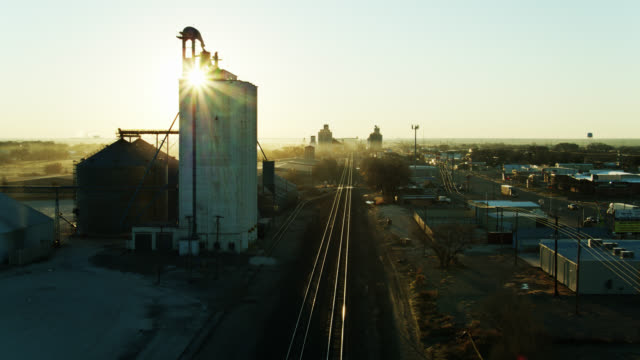 drone flight along train tracks running through small town in texas at sunrise - storage tank stock videos & royalty-free footage
