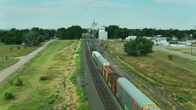 drone flight alongside freight train approaching grain elevator in nebraska town - freight elevator stock videos & royalty-free footage