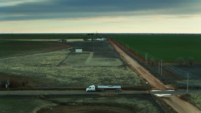 stockvideo's en b-roll-footage met dronevlucht naast melktanker die tussen weiland met koeien op achtergrond drijft - aanhangwagen