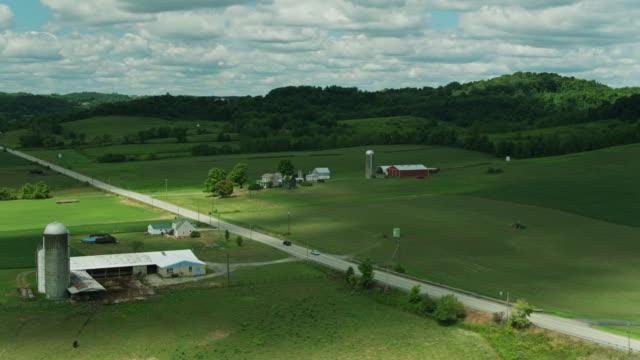 drone flight alongside road crossing rural western pennsylvania landscape - pennsylvania stock videos & royalty-free footage