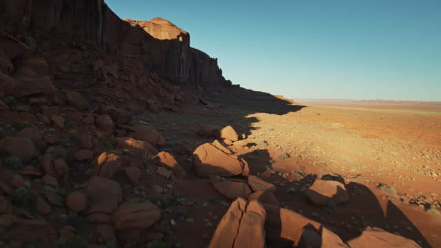 drone flight alongside rocky outcrop in monument valley - butte rocky outcrop stock videos & royalty-free footage