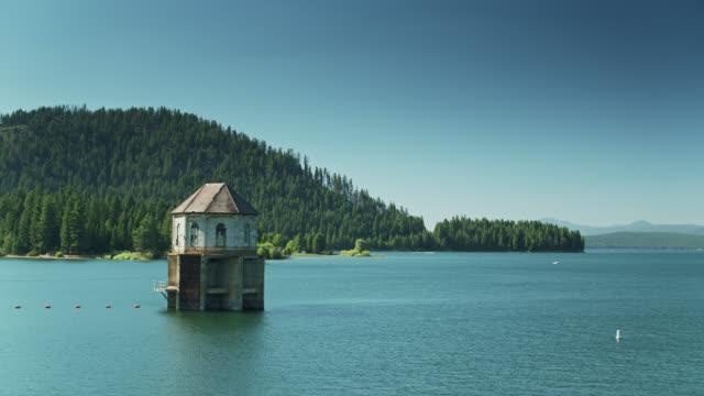 drohnenflug nähert sich pumphouse am lake almanor, ca - wasserpumpanlage stock-videos und b-roll-filmmaterial