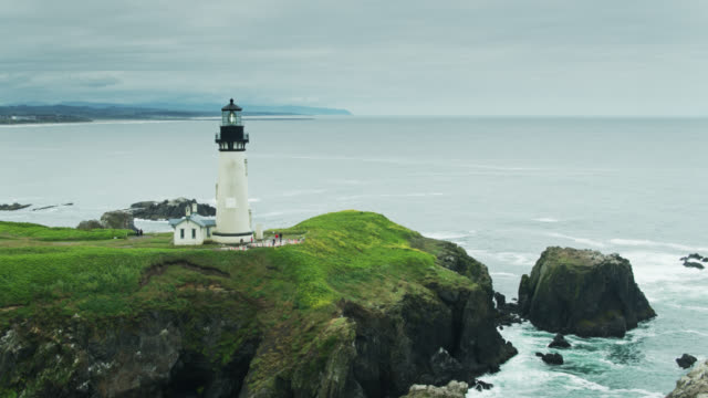 drone flight approaching yaquina head lighthouse with newport, or beyond - oregon coast stock videos & royalty-free footage